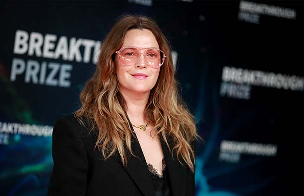 Drew Barrymore on the red carpet wearing pink sunglasses and a black dress.