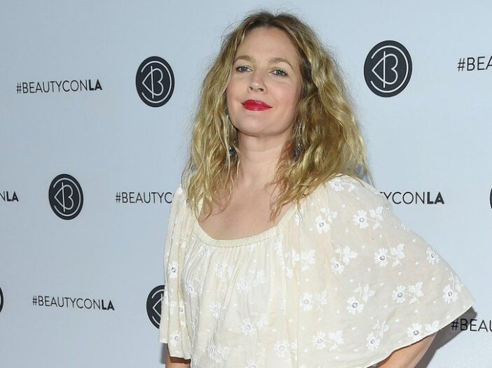 Drew Barrymore smiles in a tan and floral pattern blouse
