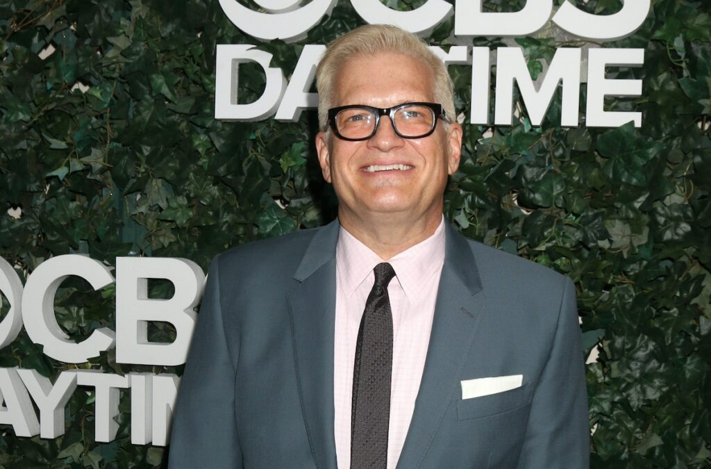 Drew Carey smiling in a blue suit