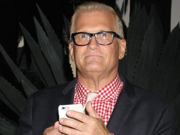 Drew Carey, wearing a black suit jacket over a red and white checkered shirt, holds up his phone