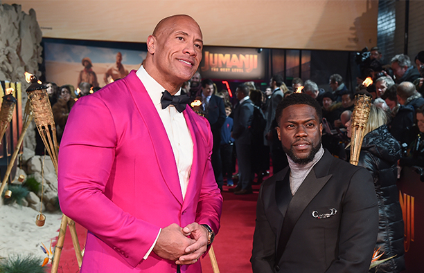 Dwayne Johnson in a pink jacket on the red carpet with Kevin Hart in a dark suit.