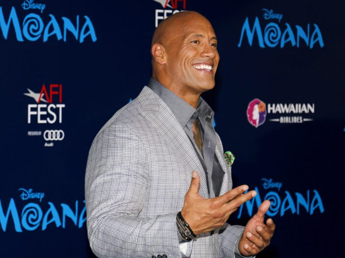 Dwayne Johnson wearing a suit and gray shirt to the premiere of Disney's Moana