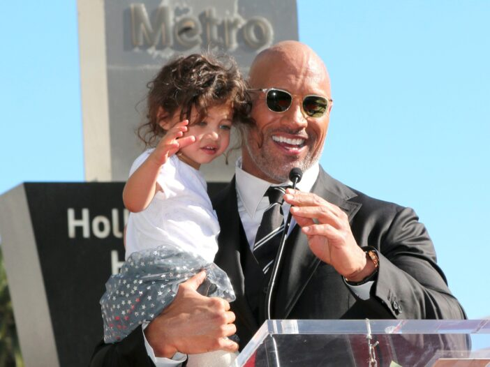 Dwayne The Rock Johnson standing at a podium holding his daughter Jasmine when she was younger.