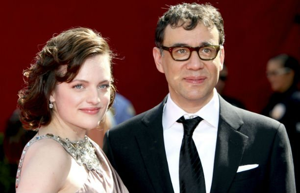 Elisabeth Moss in a pale blush colored dress standing with Fred Armisen, who's wearing a black suit,