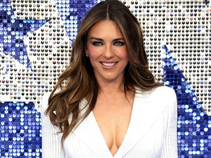 Elizabeth Hurley smiling in a buttoned white blazer against a blue background