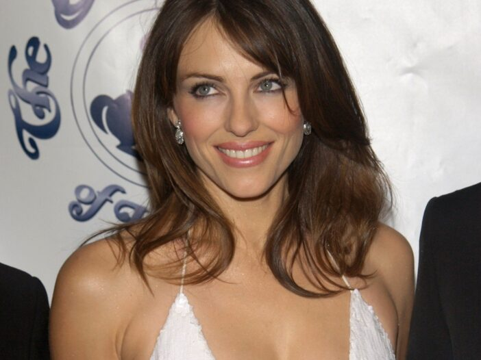 Elizabeth Hurley wears a low cut white dress against a white background