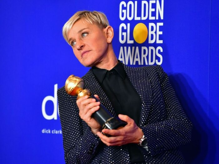 Ellen Degeneres in a dark suit and button up holding a golden aware and looking to her right