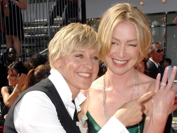 Ellen DeGeneres points at Portia de Rossi's left hand, which holds a glittering wedding band