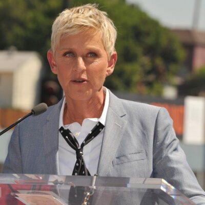 Ellen DeGeneres wearing a loosened necktie, standing at a podium.