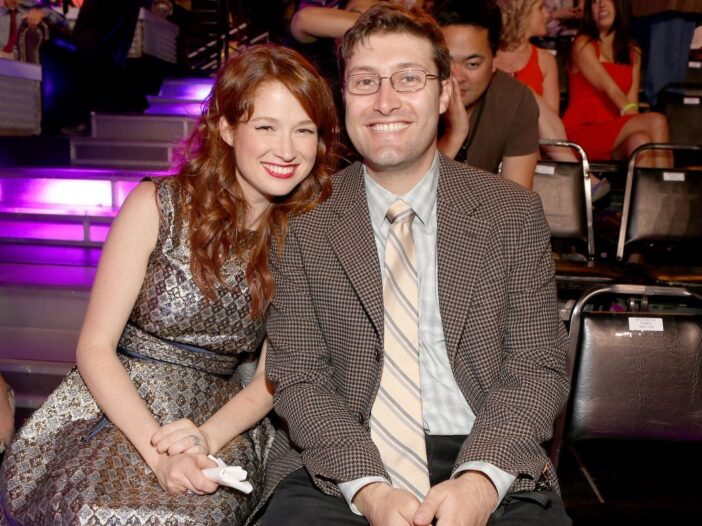 Ellie Kemper in a silver patterned dress smiles next to husband Michael Koman in a suit