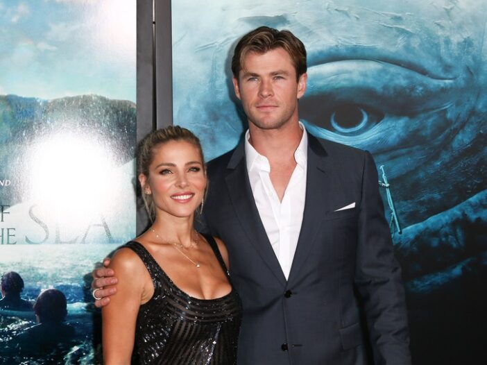 Elsa Pataky wearing a semi-sheer dress stands with Chris Hemsworth, in a gray suit, at a movie premiere