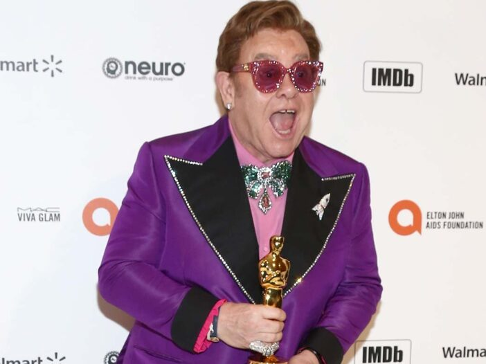 Elton John smiling and in good health, holding his Oscar, wearing a purple jacket.
