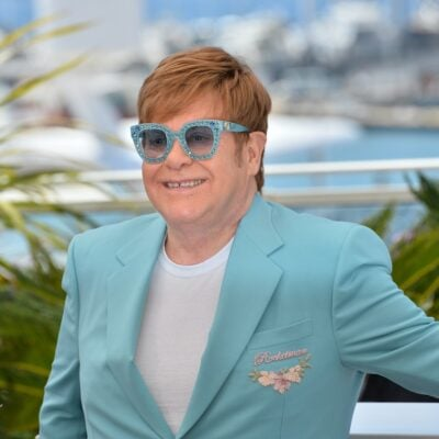 Elton John smiling outdoors dressed in a light blue jacket and white t shirt