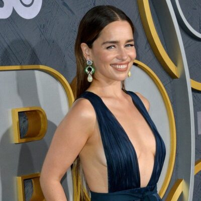 Emilia Clarke smiling in a dark blue dress on the red carpet for an HBO event