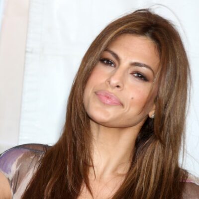 Eva Mendes, wearing a multicolored dress, stands with her hands on her hips