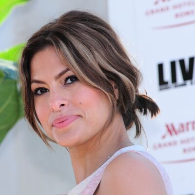 Eva Mendes wearing a sleeveless pink dress and looking over her shoulder at the photographer