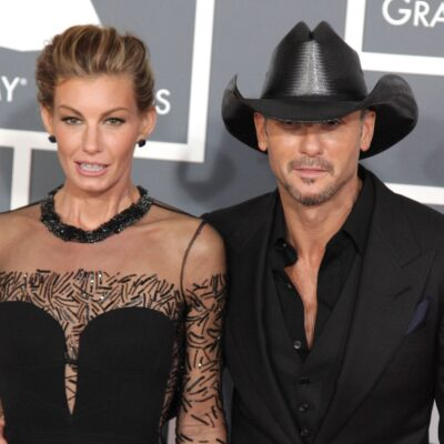 Faith Hill and Tim McGraw, both dressed in all black, walk the red carpet at the Grammy Awards