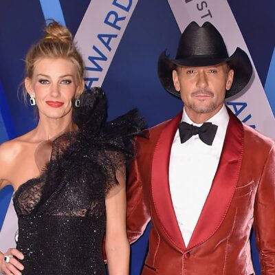 Faith Hill in a black dress smiles with her hand on hip next to husband Tim McGraw in a red tuxedo a