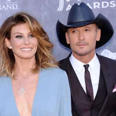 Faith Hill on the left in a light blue dress, Tim McGraw on the right in a suit and a cowboy hat.