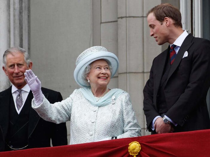 From left to right, Prince Charles, Queen Elizabeth II, and Prince William standing on a balcony at