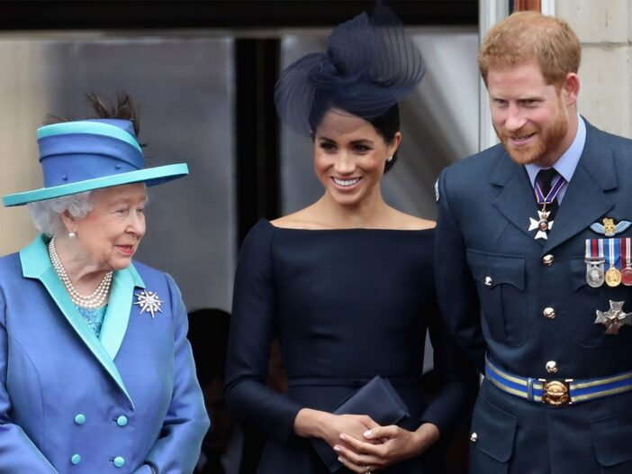 From left to right, Queen Elizabethin a blue hat, Meghan Markle in a dark dress and Prince Harry in