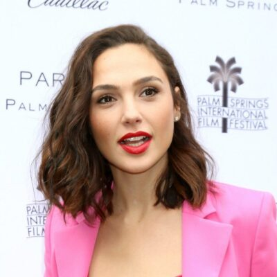 Gal Gadot talking in a pink jacket on the red carpet