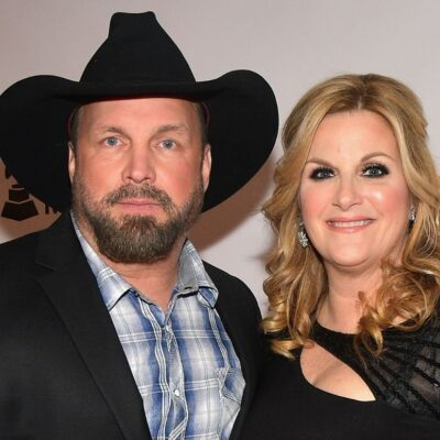 Garth Brooks wearing a suit jacket over a checkered shirt and a cowboy hat standing with Trisha Year