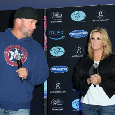 Garth Brooks wears a blue hoodie and jeans while standing with Trisha Yearwood, also casual