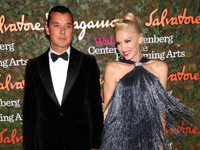 Gavin Rossdale, in a black tux, stands with Gwen Stefani, in a feathery dress