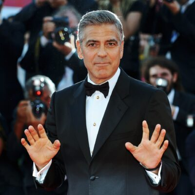George Clooney in a tux, holding up 10 fingers.