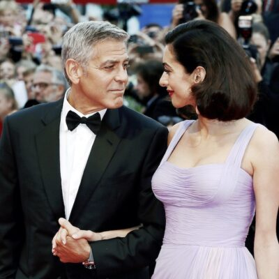 George Clooney in a tux smiling and holding hands with Amal Clooney in a purple dress