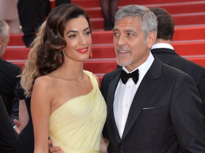 George Clooney in a tuxedo on the right with his arm around Amal Clooney in a yellow dress.