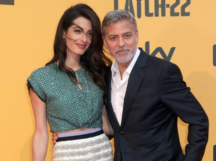 George Clooney with his arm around Amal Clooney