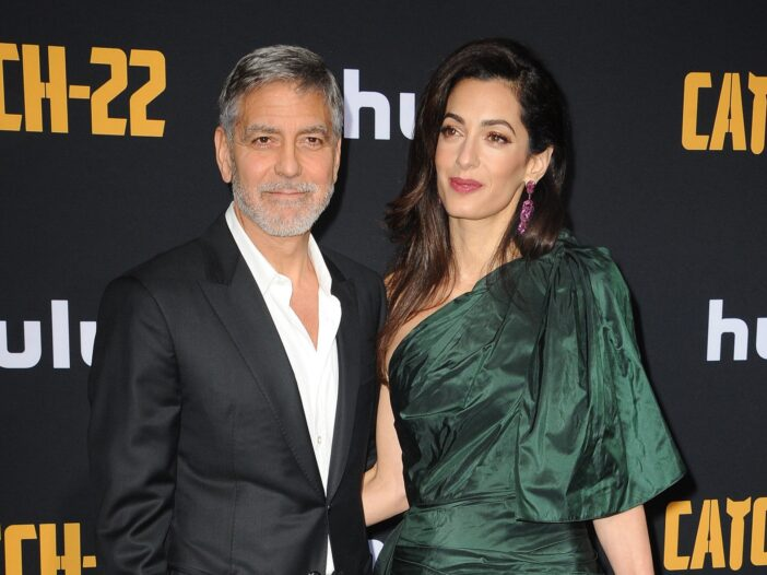 George. looney on the left in a suit. Amal Clooney on the right in a green dress, together at a movie premiere.