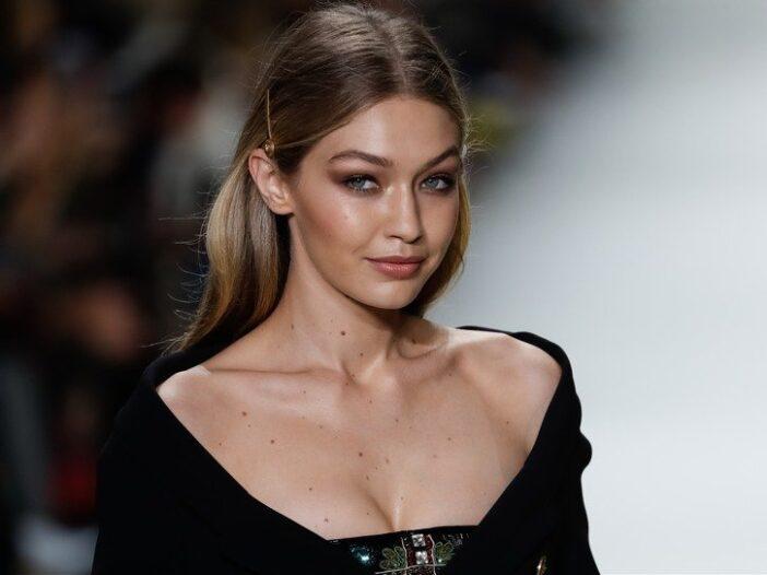 Gigi Hadid wearing a black dress while walking the catwalk during a Versace fashion show in Milan