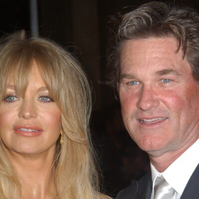 Goldie Hawn and Kurt Russell wearing evening wear pose for photographers