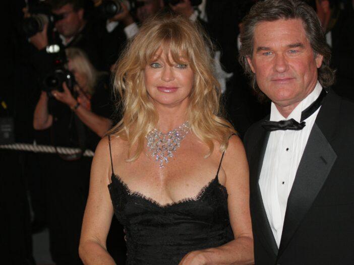 Goldie Hawn, in a black dress, stands beside Kurt Russell, who wears a black tux