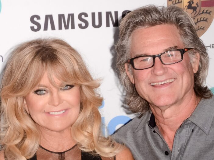 Goldie Hawn on the left, Kurt Russell on the right, both smiling.