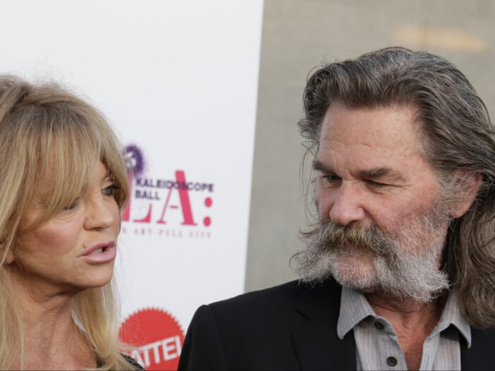 Goldie Hawn speaking to an interviewer with Kurt Russell watching at the 3rd Annual Mattel Children's Hospital Kaleidoscope Ball.