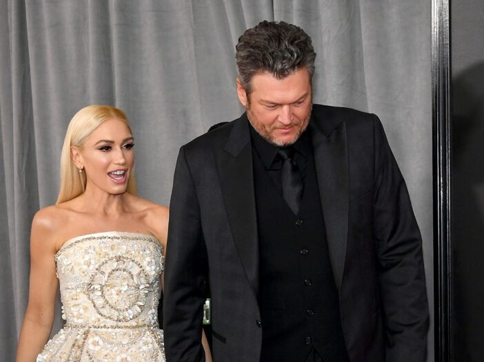 Gwen Stefani and Blake Shelton holding hands at a red carpet event.