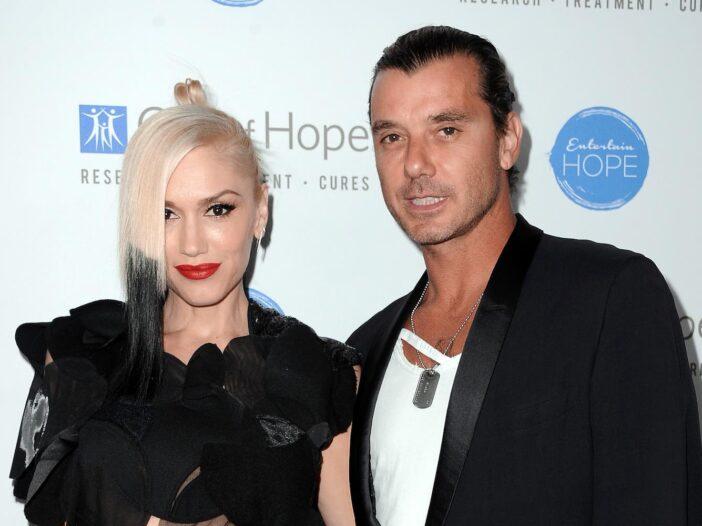Gwen Stefani in a black dress smiling next to ex husband Gavin Rossdale dressed in a black suit jack