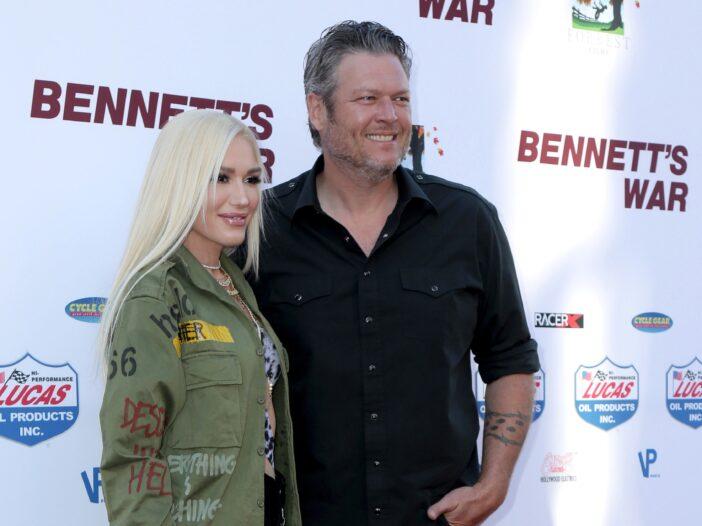 Gwen Stefani, wearing a green jacket, poses with Blake Shelton, wearing a black shirt