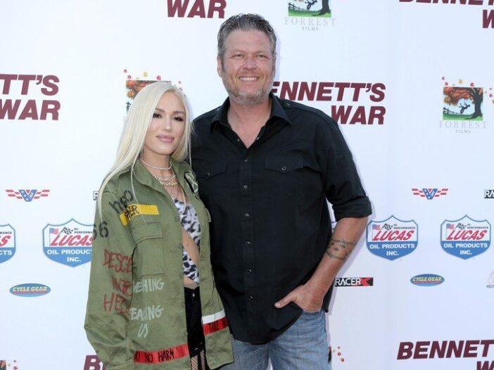 Gwen Stefani wearing a green jacket and posing with Blake Shelton, wearing a black shirt