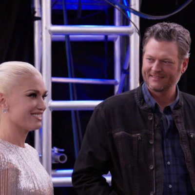 Gwen Stefani wearing a silver, sparkly fringe dress standing with Blake Shelton, who's wearing a dar