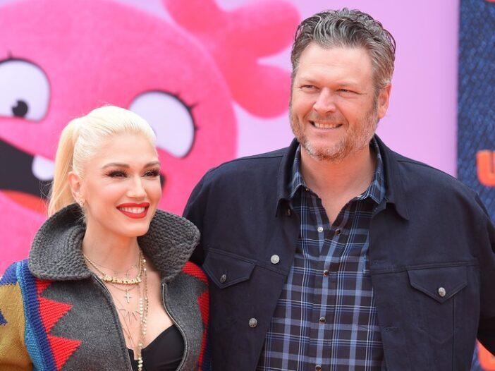 Gwen Stefani, wearing multicolored jacket, posing with Blake Shelton at the _Ugly Dolls_ premier