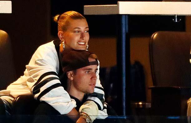 Hailey BAldwin hugging Justin Bieber in a box at a hockey game