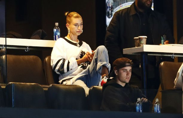 Hailey Baldwin wearing a white jersey sitting above Justin Bieber, who is wearing a black hoodie and