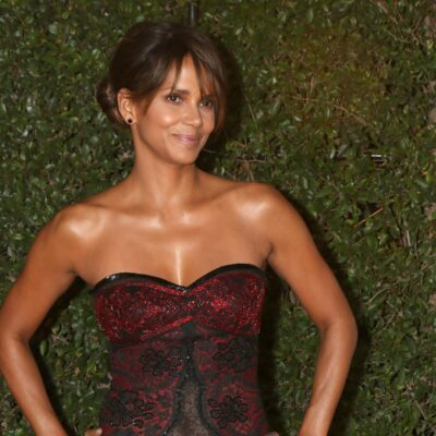 Halle Berry poses with her hands on her hips while wearing a red and black dress