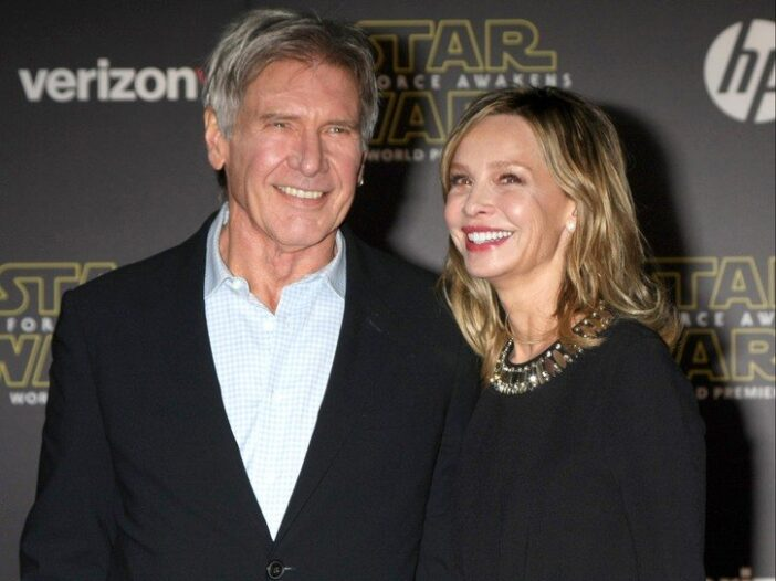 Harrison Ford wearing a black blazer stands with Calista Flockhart at a Star Wars premiere