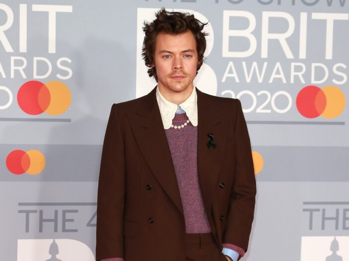 Harry Styles wears a brown suit over a pinkish sweater and pearls at the Brit Awards